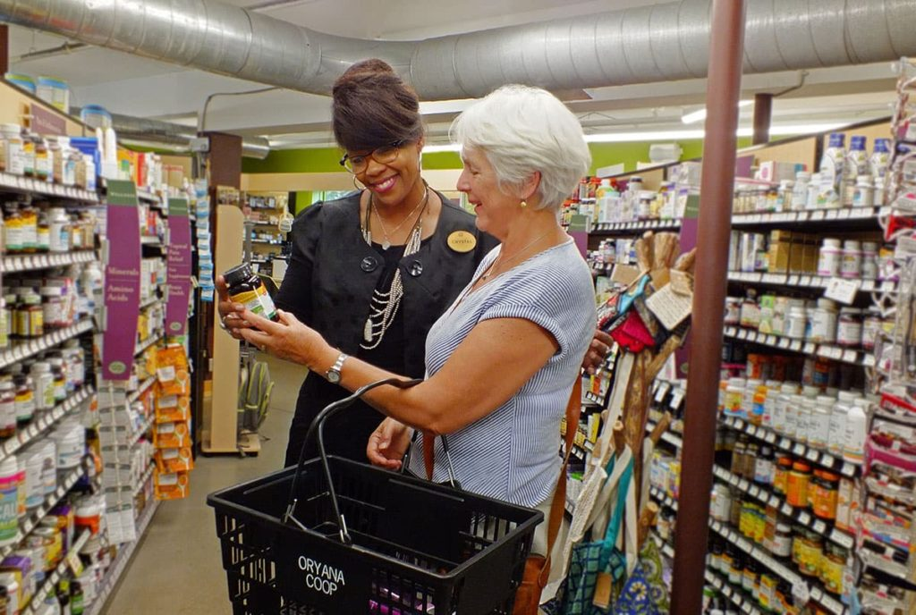 An Oryana employee assisting a customer with supplement selection
